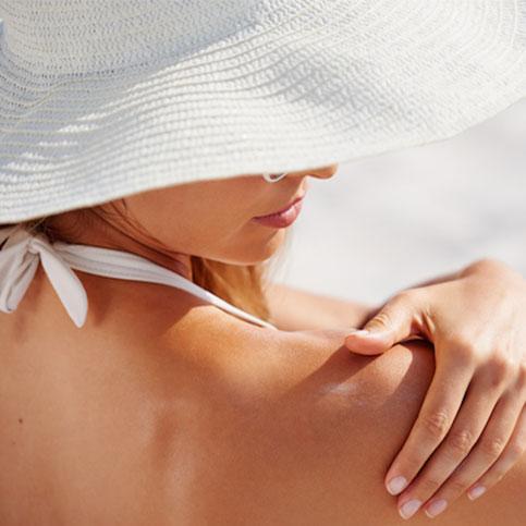 Frau mit weißem Hut cremt sich ihre Schulter ein