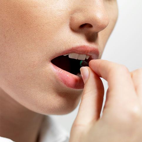 Frau nimmt eine Tablette gegen ihre Allergiesymptome