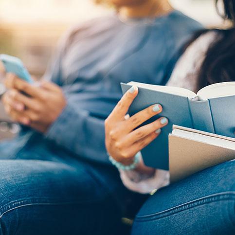 Frau liest ein Buch und Mann schaut auf sein Handy